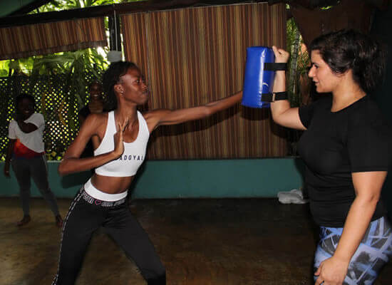 Photograph of a young woman punching a punching pad